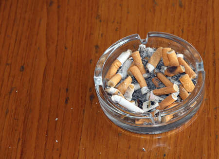 chock: ashtray chock full of cigarette butts and smoke a lot of ash Stock Photo