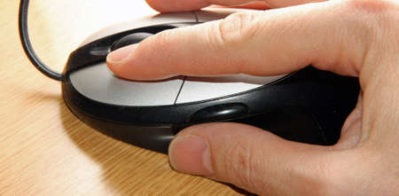 confirms: hand of a young adult who click the left mouse button with the index Stock Photo