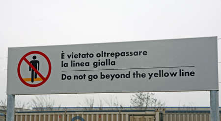inscription of the cartel does not cross the tracks in the italian rail station photo