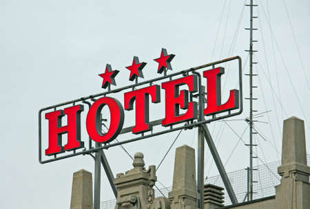overnight stay: Huge written three star HOTEL above the roof of a building in the city