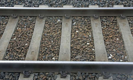 parallelism: train track with sleepers and Rails where stones passing freight train
