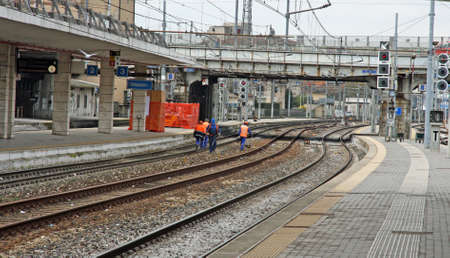 workers with the jacket reflective piping for safety at work in the middle of the tracks of a train station