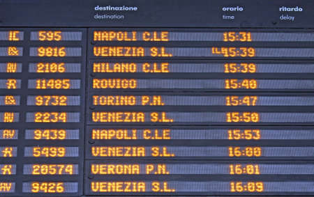 Board schedules of arrivals and departures of trains in an Italian train station