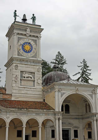 clock of the moors: ancient Bell Tower with two African statues over flying hours in the town of Udine in Italy