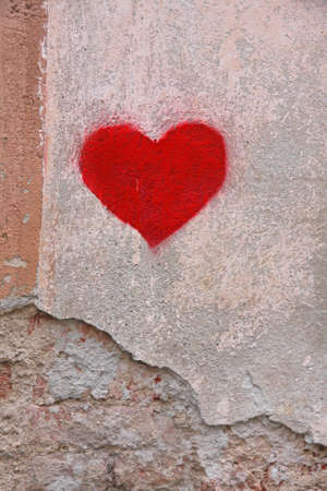 bright red heart drawn by a lover on a wall photo