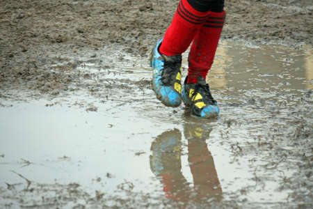 muddy soccer shoes of a child player during a football match in a playing field full of mud