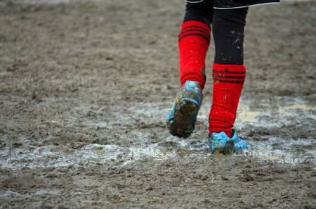 muddy soccer shoes of a child player during a football match in a playing field full of mud photo