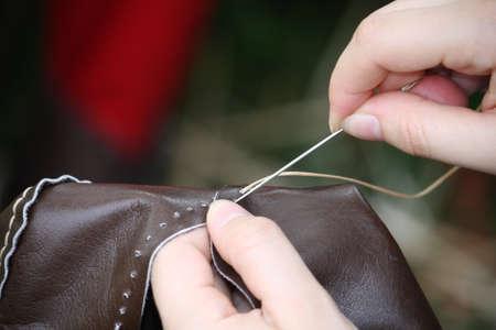 craftsman: mujer mientras está cosiendo un vestido en cuero con aguja e hilo