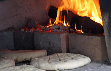 focaccia: loaves and pieces of raw bread cooked in the wood-fired oven Stock Photo
