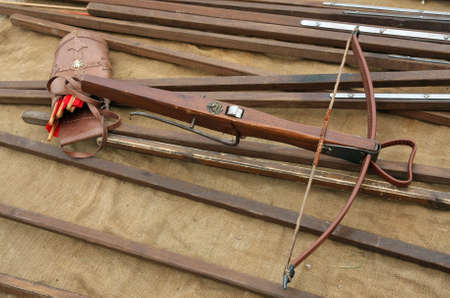 weaponry: wooden crossbow with arrows and other ancient