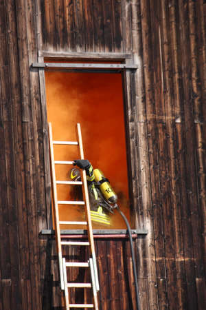 brave firefighters with oxygen cylinder goes into a house through a window during a fire photo