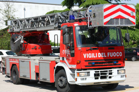 truck with ladder of the fire brigade arrives in speed at the place of the dangerous fire photo