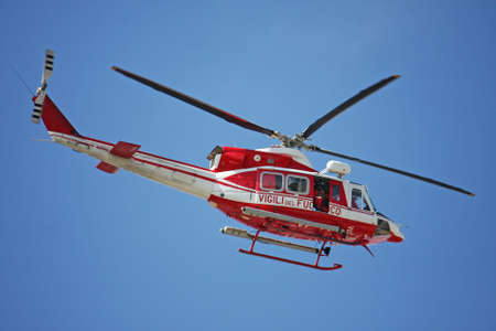 patrol helicopter of firefighters in blue sky over a fire 4 Stock Photo - 19598822