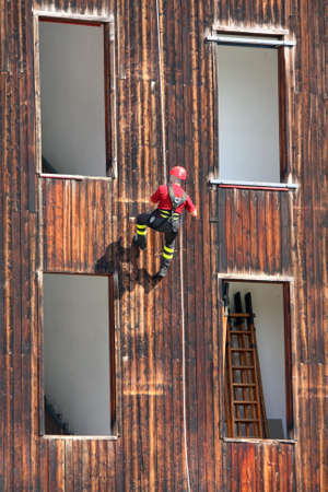 abseiling: Fireman in uniform by climber and rock climber while descending from a House to save people in danger Stock Photo