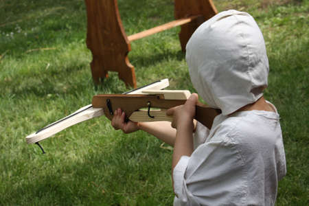 soldier fish: young child medieval soldier practices with the crossbow and arrows