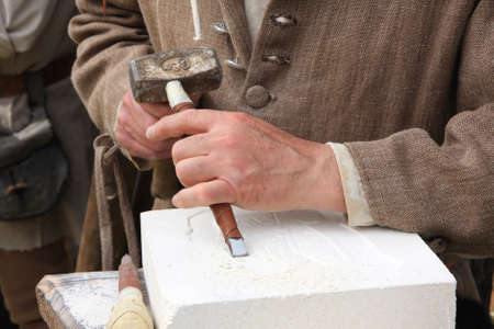 chisel: old craftsman Mason during the processing of a piece of white marble