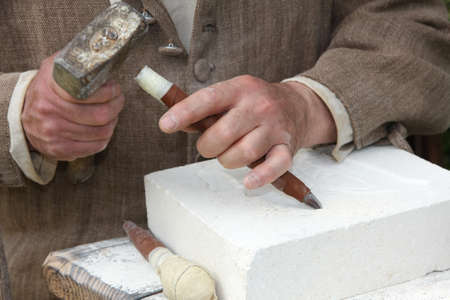 sculpting: old craftsman Mason during the processing of a piece of white marble