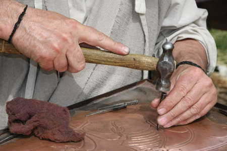 art processing: old craftsman Mason during the processing of a copper with an engraver and hammer Stock Photo