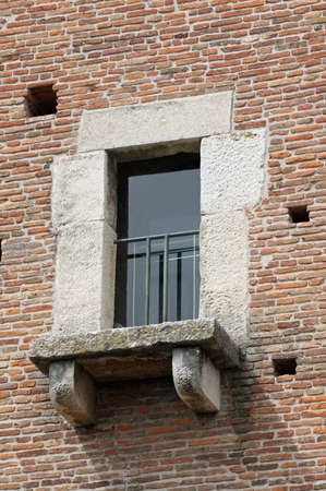 balcony window of an ancient medieval tower made of red bricks photo