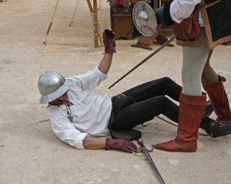 mortally: ancient medieval costume with soldier mortally wounded while simulating in a hand-to-hand combat