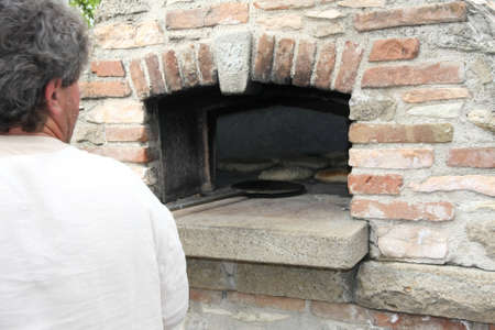 woodfired: Baker during the preparation of loaves of bread baked in the wood-fired oven