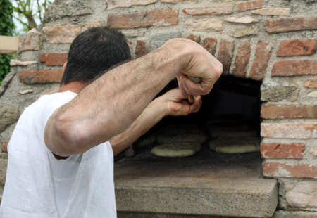 muscled: muscled Baker when baking bread in a wood-burning oven