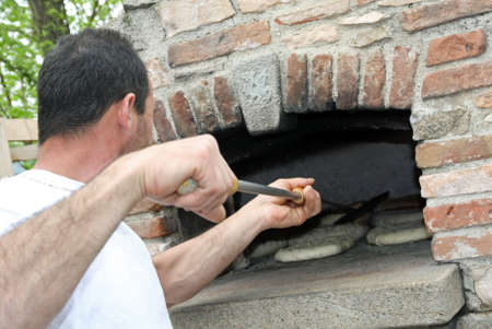 woodburning: muscled Baker when baking bread in a wood-burning oven