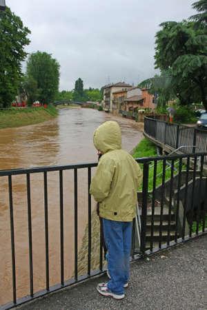 sgomento: bambino con orologio da polso impermeabile con sgomento il livello del fiume cresce