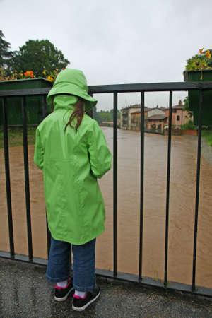 sgomento: giovane ragazza con orologio da polso impermeabile con sgomento il livello del fiume cresce Archivio Fotografico