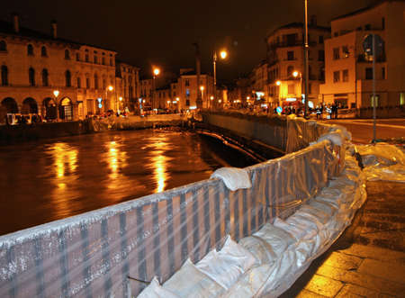bridge in town with sandbags during a flood in Italy