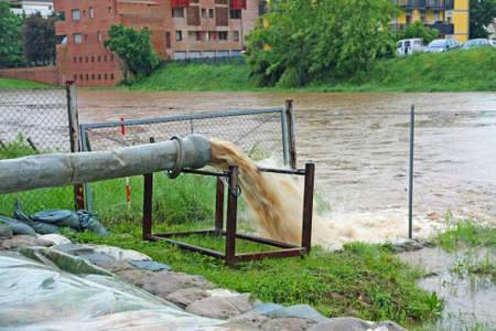 overflows: impressive exhaust flows into river rainwater and mud Stock Photo