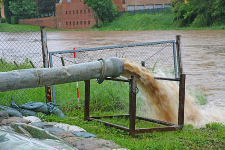 hazardous waste: impressive exhaust flows into river rainwater and mud Stock Photo