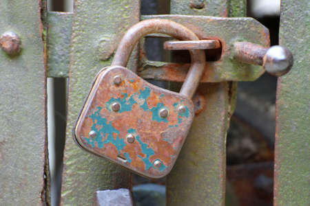 old rusty padlock that closes the scratch of an ancient prison of bandits photo