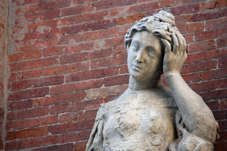 keep your hands: ancient statue with headaches and the brick wall Stock Photo