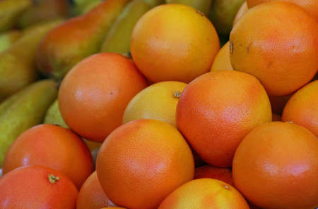 Orange grapefruit and ripe pears sold by greengrocers photo