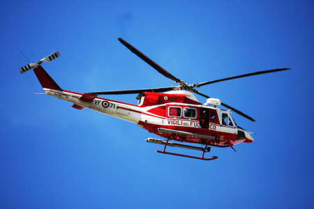 patrol helicopter of firefighters in blue sky over a fire