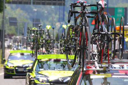sponsors: powerful machines with bicycles flagships Commons follow cyclists during the cycling race in the street