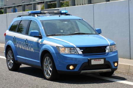 Blue Italian police car whizzes quickly in the middle of the road in the city photo