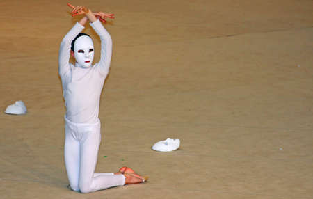 anonymity: dancer with white mask during a show at the theatre
