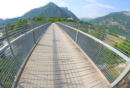 long bridge with a wooden walkway and handrail made of galvanized steel photo