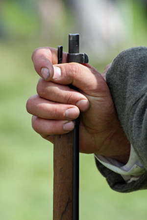 a soldier's hand with dirty fingernails while holding the barrel of a gun photo