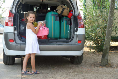 loads: Nice thoughtful little girl with white dress loads the car for the holidays