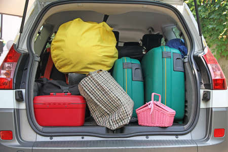 holidays vacancy: two green suitcases and many bags in the trunk of the car ready to depart for the holidays