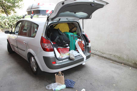 Car full of suitcases and bags to return from summer holidays Stock Photo