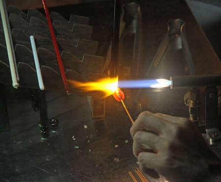 glazier: Glazier with gas torch lit while blending and shaping a piece of glass 2