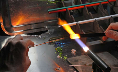 glazier: Glazier with gas torch lit while blending and shaping a piece of glass 5