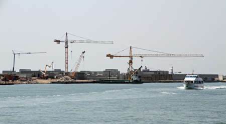 huge cranes for the construction of a dam and boat passengers photo
