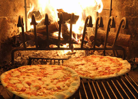 excellent fragrant pizza baked in a wood fireplace with a wood-burning oven pizzeria 1 Stock Photo