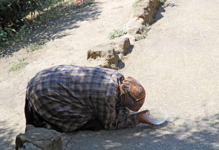 marginalized: poor old Gypsy woman begging for pedestrians on the street
