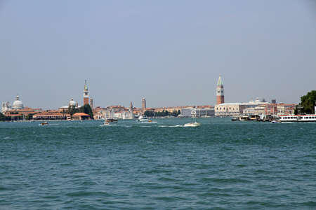 bedlam: skyline of Venice with bell tower, boat and ferry in the Adriatic Sea in Italy Stock Photo